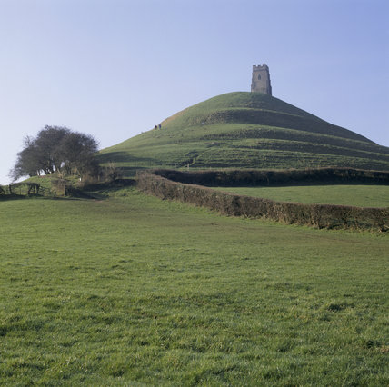 View across a field to Glastonbury Tor with the C15th tower at the summit and a couple of walkers on the hillside