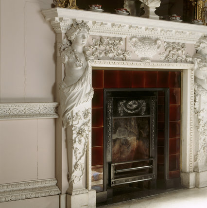Detail of Bacchic caryatid clad in lion skins and crowned with vine wreaths on left side of fireplace in The Great Red Room