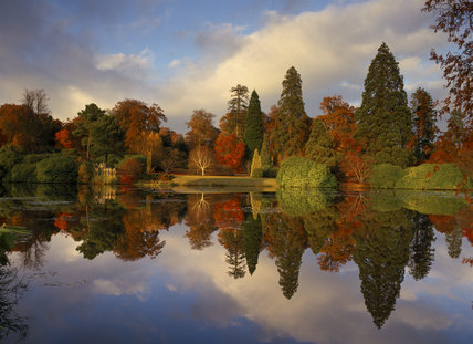 An almost perfect reflection of Autumn colour in the Middle Lake at Sheffield Park from pale pampas grass, and deep green rhododendrons to gold, orange and red acers