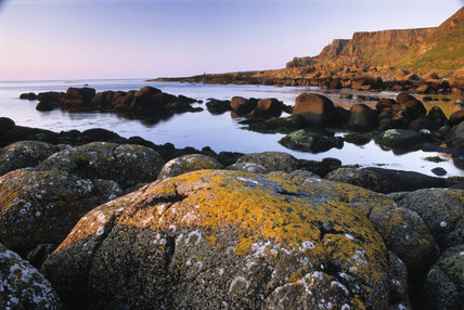Distant view of headland and inlets, huge boulders in the foreground, taken at sunset at The Giant's Causeway