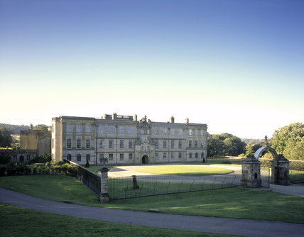 View of the Lyme Park arched entrance to the Forecourt, gate- piers and iron railings, and the North Front in a mix of 16th, 17th and 18th Century styles