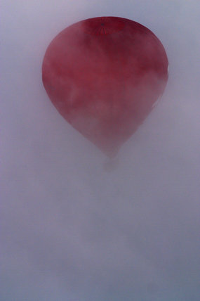 A hot air balloon from the Blickling Balloon Festival flying in mist over East Anglia near Blickling Hall
