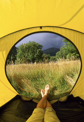 Close up view of male camper's crossed legs in a tent, on the NT campsite at Wasdale Head, Cumbria