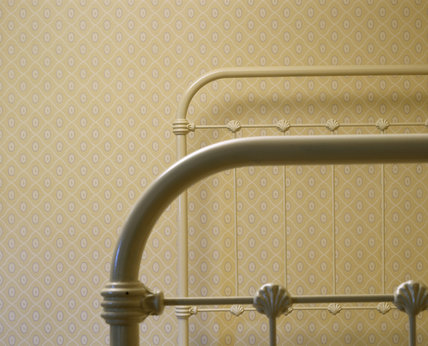 Detail of a 1930s white painted iron bedstead with shell design, against a daisy patterned wallpaper on a pale yellow background in the second floor bedroom of the Birmingham Back to Backs