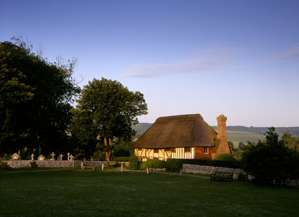 Alfriston Clergy House seen from the village green in the last rays of the setting sun