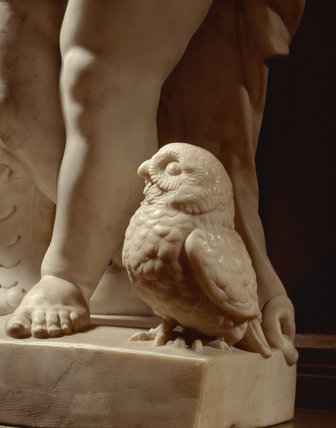 Detail of owl at the base of a marble statue of a cherub, in the Long Gallery at Powis Castle