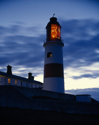 The Lighthouse at Souter showing a red light at dusk, against a dramatic sky