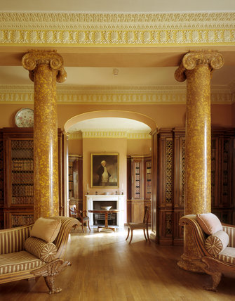 The Library at Melford Hall looking south through archway showing a pair of scagliola columns either side of the arch and two chaise longues