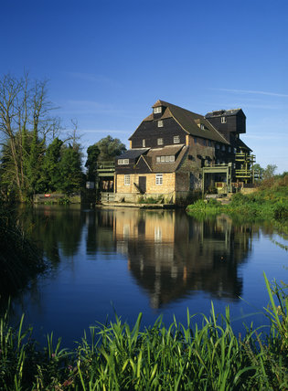 The weatherboarded Houghton Watermill on the river Ouse