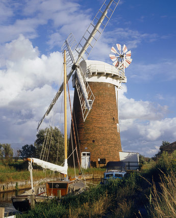 Horsey windmill at Horsey Mere in the Norfolk Broads, a sailing boat with sail down, in the foreground