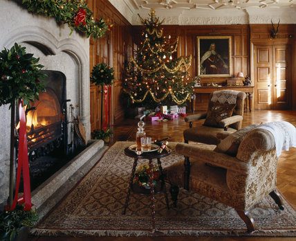 A cosy Christmas scene in the Outer Hall, with a decorated tree, surrounded by presents, a blazing fire and a drink awaiting the expected occupent of the armchair