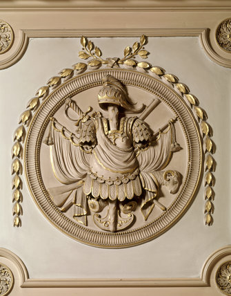 A detail of armorial trophy in roundel above the door in the Marble Hall