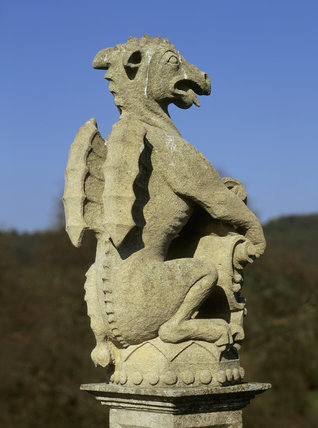 Close-up of a carved stone mythical winged beast, atop a column