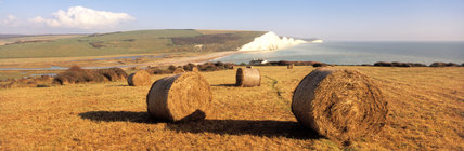 View of hay bales at Seven Sisters looking towards the sandy beach and sea
