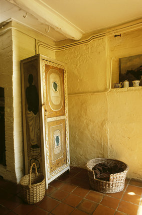 The painted cupboard and baskets in the kitchen at Monk's House