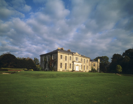 The West Front of the Argory seen from across the lawn with stormy sky behind