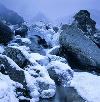 Snow covered ice formations on the river below Llyn Idwal, with a misty Y Garn in the distance