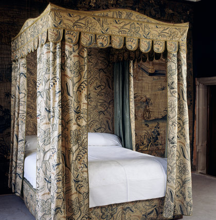 The mahogany bed in the Lawn Room dates from the 19th century but the wool on linen crewel work bed hangings are 17th century