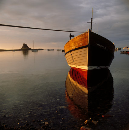 Reflection of a fishing boat in the still waters of the harbour with Holy Island and Lindisfarne Castle on the horizon