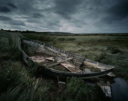 The remains of a small boat rotting away on the saltmarshes at Morston, beneath a menacing sky