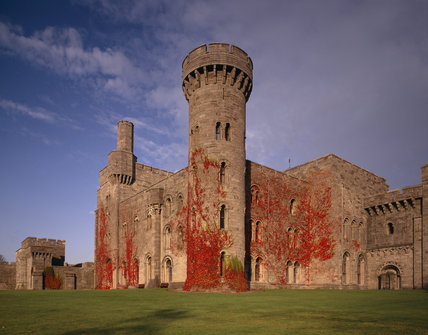 A red autumnal creeper covers the exterior walls of the Library and the passage to the Keep