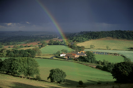 A farmstead amidst fields in the Clent Hills, Hereford & Worcester,  bathed in sunshine, with a rainbow rising up against the dark sky