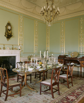 The State Dining Room at Chirk Castle showing the fireplace, chandelier, table and chairs