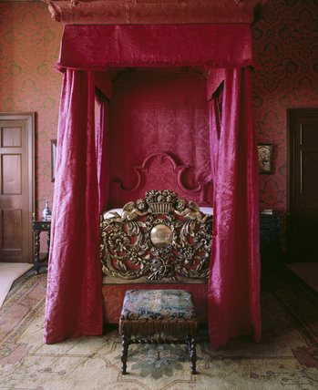 Close-up view of the State Bed in the King's Bedroom at Chirk Castle, showing the crimson silk damask hangings