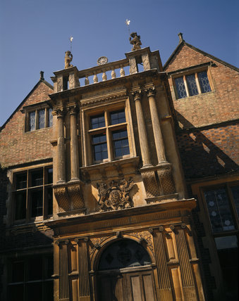 The porch above the main doorway at Charlecote Park emblazoned with the arms of Queen Elizabeth I and surmounted with corinthian columns and dog-like animals