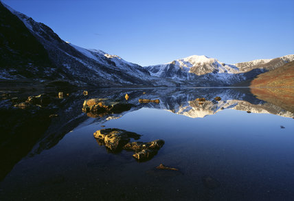 Llyn Ogwen, still waters at dawn with the snow-capped peak of Y Garn catching the early sunlight