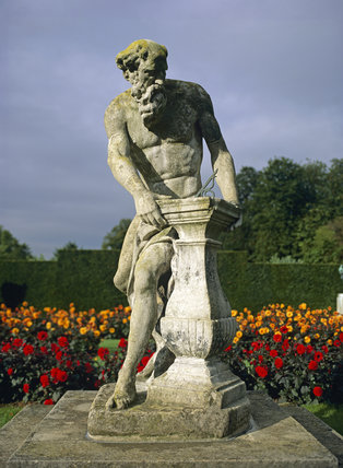 Statue of Old Father Time with a sundial, English 1700, in the gardens at Anglesey Abbey