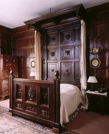 The oak bedstead and Chinese Chippendale tallboy by Gillow in the Bindloss Room at Sizergh Castle