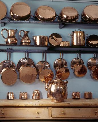 The copper pots and pans on the shelves in the kitchen at for Art and cuisine ceramic cookware