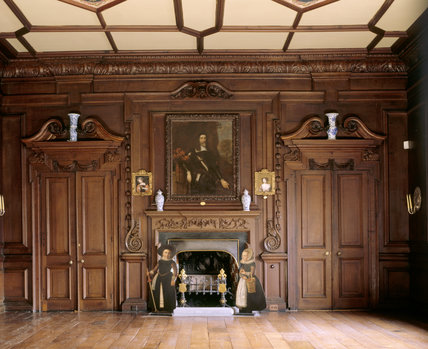 Partial view of the Rococo carved chimneypiece and dummy-board figures of children at the Chapel end of the Long Gallery at Chirk Castle