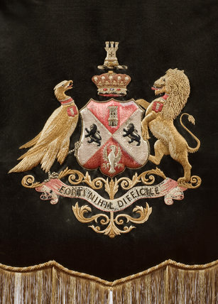 The Beaconsfield arms embroidered by Hannah de Rothschild, Lady Rosebery, on a silk banner firescreen with a bamboo style frame in the Library at Hughenden Manor, High Wycombe, Buckinghamshire