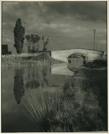 Man Fishing next to Unidentified Bridge