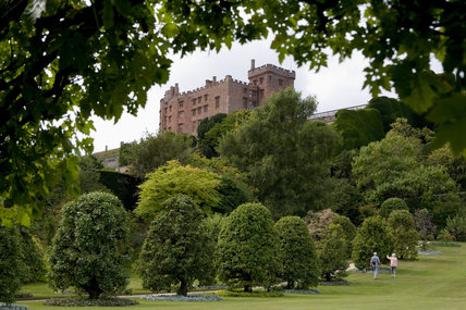 The medieval castle looms over the grounds with a couple of visitors admiring the view at Powis Castle & Garden, Welshpool, Powys, Wales