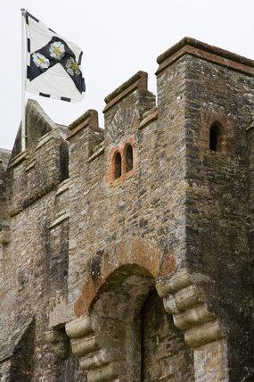 Flag flying above the main portcullis entrance at Compton Castle, Devon