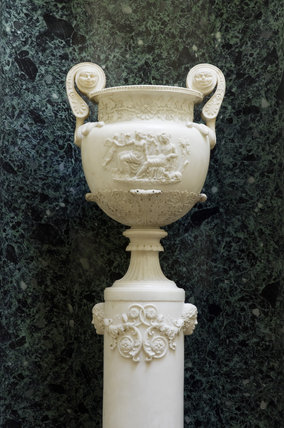 An urn with decorative faces in the Upstairs Corridor at Hinton Ampner, Hampshire