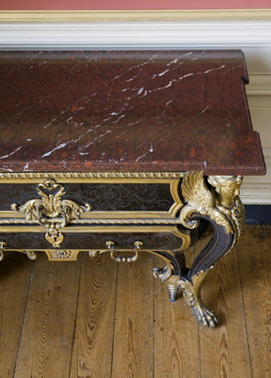 View of the marble top and cabriole leg of the Boulle commode in the Carved Room at Petworth House, West Sussex