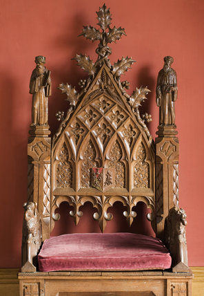 Neo-Gothick oak armchair carved by John Baldwin in 1863 and bearing Disraeli's coat of arms, in the Garden Hall at Hughenden Manor, High Wycombe, Buckinghamshire