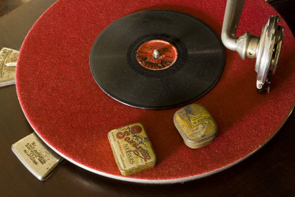 Columbia Grafonola wind-up gramophone player turntable, with a record and tins of spare needles, in the Parlour at Plas yn Rhiw, Pwllheli, Gwynedd