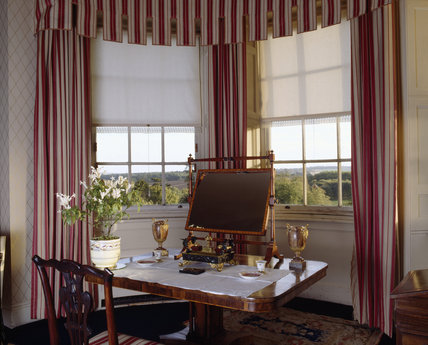 Hinton Ampner, view of the regency rosewood breakfast table with George III satinwood mirror in Mrs Duttons Bedroom showing full length striped curtains and blinds