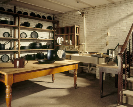 View of the Scullery facing sink with pots and pans on the table