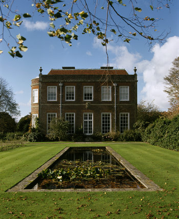 View from pool garden with water-lilies to the east front of Hinton Ampner, a late 18th century house remodelled in 1869
