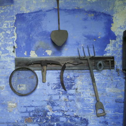 Old gardening implements on a peeling blue painted wall, in the gardener's bothy at Calke Abbey