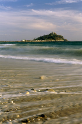 Distance view, in sunshine with cloud cover, of St.Michael's Mount, originally the site of a Benedictine Abbey, showing the castle, white buildings underneath and the sea at high tide.