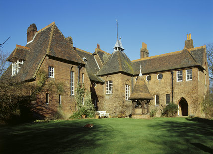 Exterior view of Red House built for William Morris by Phillip Webb, 1859-60, showing the inner side of L shaped building, with staircase tower, hipped and pitched roofs, and chimneys
