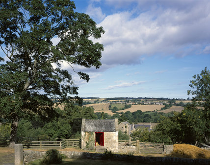 Close view of the front of the Poultiggery [pig-henhouse-dove- house] at Cherryburn, birthplace of Thomas Bewick, showing the rough sandstone building with the farmhouse and farmland beyond