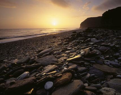 The sun rising over the sea near Fox Holes Dene on the Durham coast, lighting the rocks and pebbles